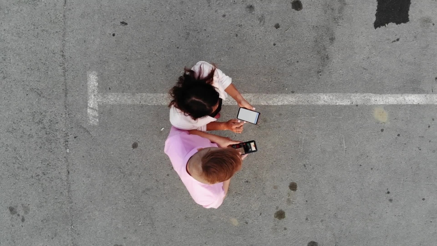 Aerial drone shot of young pretty couple of business partners use smartphones | Shutterstock HD Video #1041106012