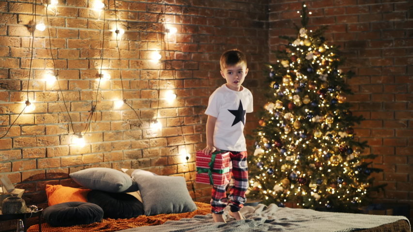 Cute little boy of 4 year old holding gift box and jumping on bed with excitement in cozy bedroom decorated with Christmas tree and garland | Shutterstock HD Video #1041137482