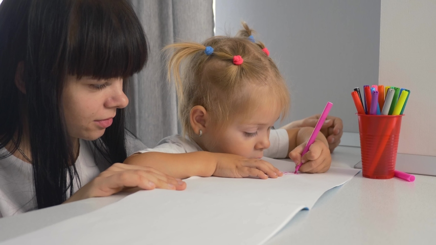 Happy family. Mom and daughter draw a picture in the album. Home schooling. Doing homework. Teamwork | Shutterstock HD Video #1041222052