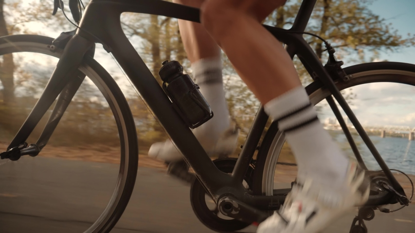 Cycling Athlete At Sunset Fall On City.Gear System Road Bicycle And Bike Wheel Rotation.Close-Up Cyclist Pedaling On City Park At Autumn.Cyclist Twists Pedals And Riding On Road Bicycle.Sport Concept | Shutterstock HD Video #1041230422