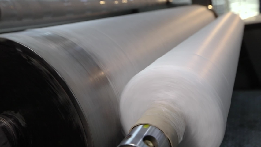 Rolls of non-woven fabric are being pushed into the tube. Nonwoven fabric production | Shutterstock HD Video #1041254032