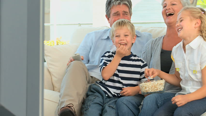 Family watching tv while eating popcorn in the living room