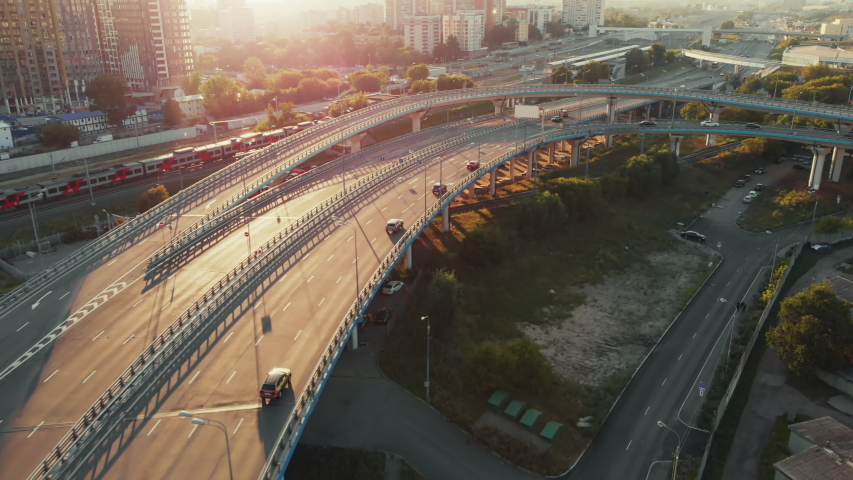 Beautiful top side view to the cars driving on multi-level highway on the sunny evening in Moscow. Picturesque aerial panorama of the road traffic and sunset city. | Shutterstock HD Video #1041369862
