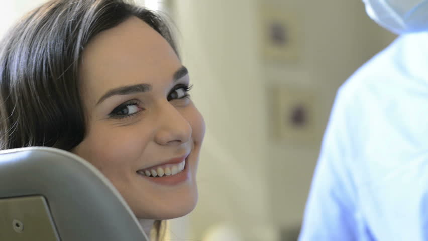 Smiling young woman receiving dental checkup. Portrait of a smiling woman looking at camera after visiting  the dentist. Male dentist examining the teeth with a mirror.