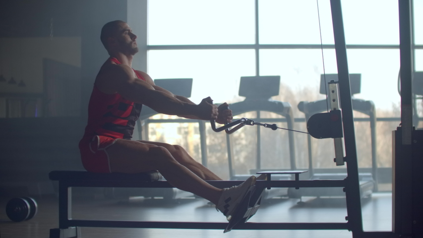 Young man doing workouts on a back with power exercise machine in a gym club. At athletic man doing workouts on a back with power exercise machine in a gym on the background of large Windows | Shutterstock HD Video #1041418702
