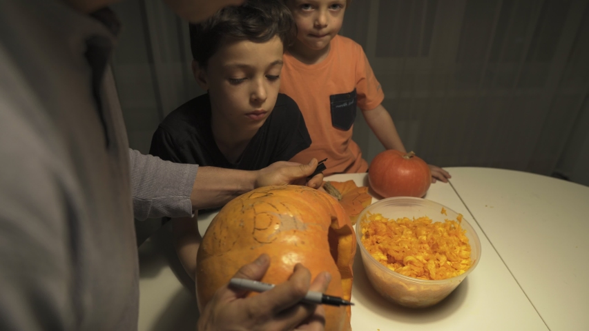 Happy halloween. Father and sons carving pumpkin on the table in the home. Family preparing for holiday. Top view. Close up. | Shutterstock HD Video #1041456592