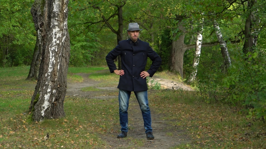 Business man in hat and coat in the woods dancing disco.   Shutterstock HD Video #1041457732