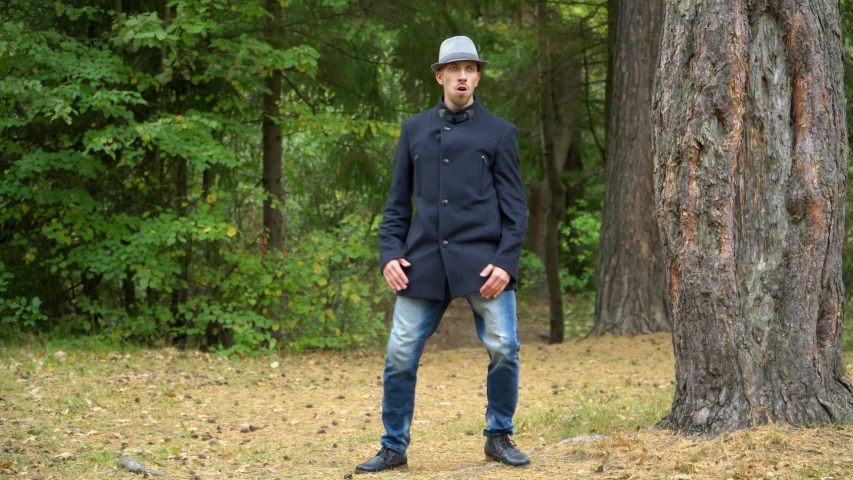 A business man in a hat and coat in the woods happily dancing touching the hat.   Shutterstock HD Video #1041457762