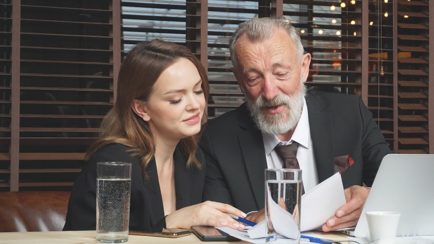 Elderly gray-haired leader stares at long-haired employee dressed in black business suit and white blouse, charming woman carefully reads paper document   Shutterstock HD Video #1041458692