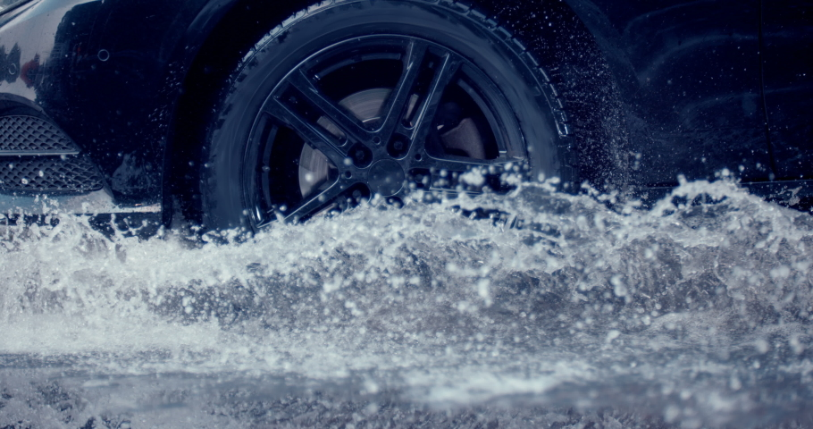 Reflecting everything around with its glossy surface, the premium car rides in extreme conditions - on a puddle on the road, where a large stream of spray erupts from under the wheels | Shutterstock HD Video #1041554272
