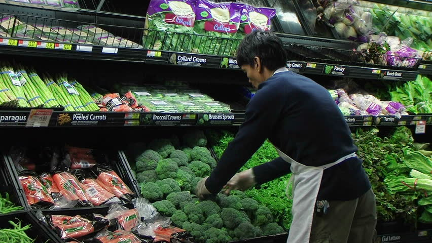 Worker facing produce display of fresh broccoli in grocery store.