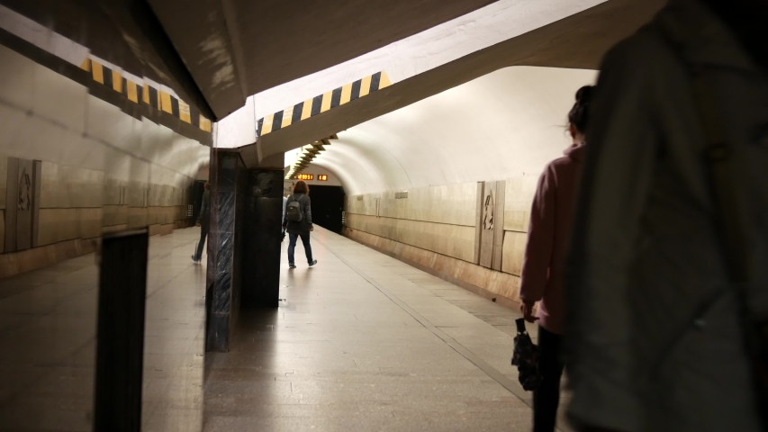 Unrecognizable woman walks along the platform in the subway. Passengers are moving from station to station. Marble and granite on the walls. USSR architecture | Shutterstock HD Video #1042105672
