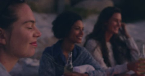 Group of friends on the beach drinking beer playing guitar with a bonfire on a summer evening RED DRAGON