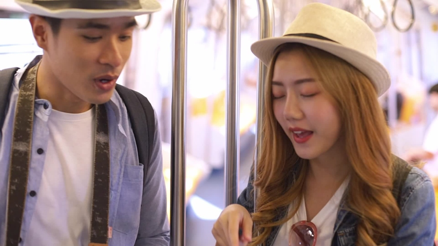 Portrait of attractive smiling Asian  couple  in train using smartphone chatting with friends woman hand internet technology cellphone city .   Shutterstock HD Video #1042273282