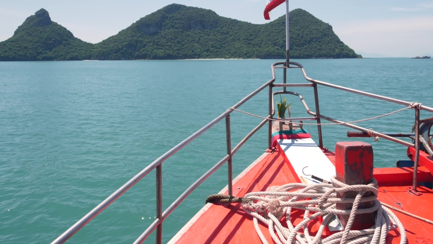 Group of Islands in ocean at Ang Thong National Marine Park. Archipelago in the Gulf of Thailand. Idyllic turquoise sea natural background with copy space. Waving flag as national symbol on the boat | Shutterstock HD Video #1042276972
