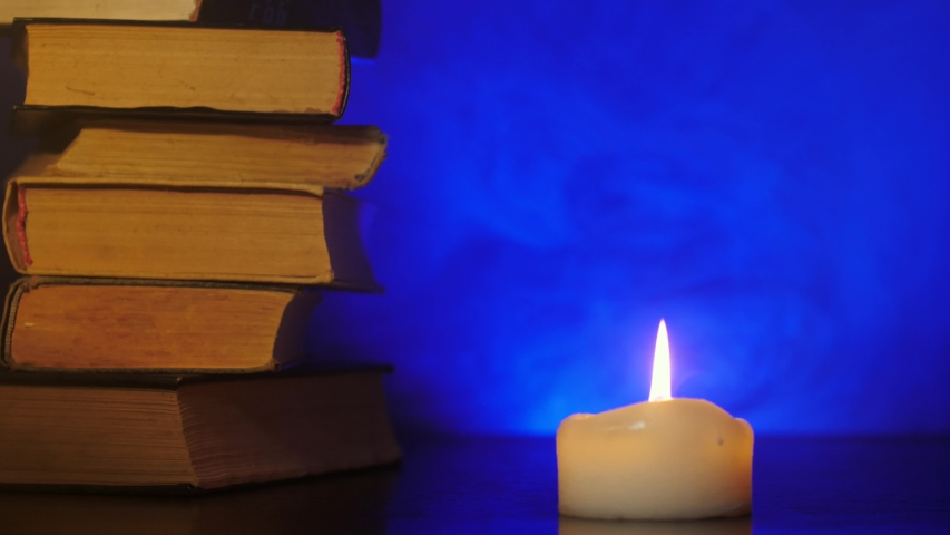 Piles of books are standing near a burning candle and colored magic smoke is flying.   Shutterstock HD Video #1042340392