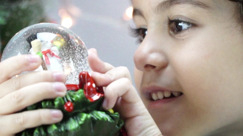 Little boy shook the snow globe, put it on the floor and peep inside it as the snow falls on the santa claus located inside this snow globe. 4K | Shutterstock HD Video #1042367302