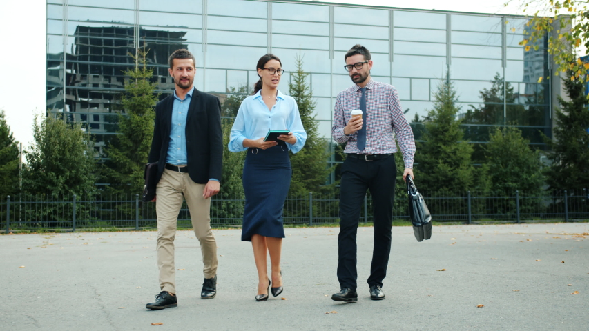 Group of young ambitious businesspeople walking together outdoors having conversation holding bags, coffee and notebook. Business and communication people. | Shutterstock HD Video #1042493092