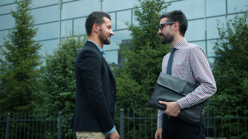 Coworkers successful young men are shaking hands outdoors saying good-bye then leaving in different directions. Human cooperation and communication concept. | Shutterstock HD Video #1042493152