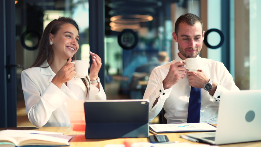 Confident executive managers communicating about business during coffee break at table desktop, successful male and female colleagues talking and smiling during collaboration meeting | Shutterstock HD Video #1042559872