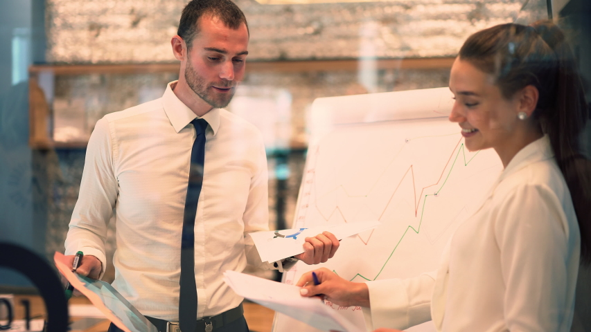Male and female colleagues brainstorming on idea for business startup using board for noting information, Caucasian partners cooperating near flip chart during presentation meeting  | Shutterstock HD Video #1042559962