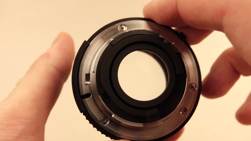 Hand holding the lens in the hand and twisting the aperture on it | Shutterstock HD Video #1042581382