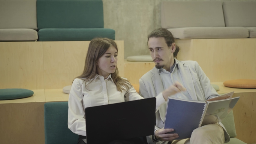 Portrait of creative male and female office workers discussing project in open space office. Young confident Caucasian man and woman sitting in innovative coworking and talking. Business, discussion. | Shutterstock HD Video #1042585072