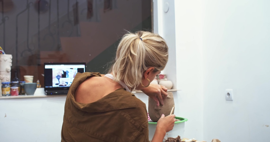 Closeup portrait of pretty blonde woman studying in modern craft studio, smiling and looking at camera. Creating clay flowerpot. Pottery coworking space. Online education. Working laptop on background | Shutterstock HD Video #1042593382