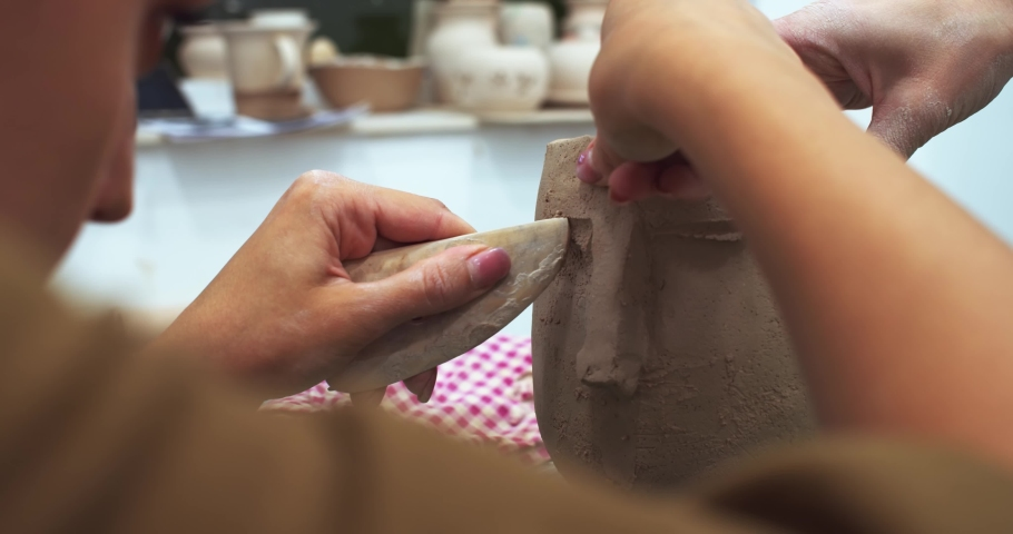 Female potter master hands creating male face eyes on raw clay flowerpot bowl in handcraft classroom in the evening. Creative hobby. Artistic lifestyle. Art education on distance. Craft workshop. | Shutterstock HD Video #1042593562