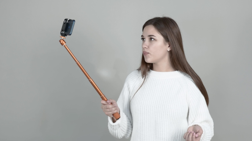 Grey background Caucasian girl blogger white cardigan long straight hair brown haired holds cellphone speaks, waves, communicates with followers | Shutterstock HD Video #1042617832