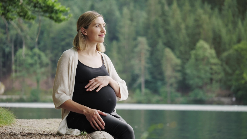 Pregnant woman touching gently her tummy when sitting near the mountain lake. #1042719652