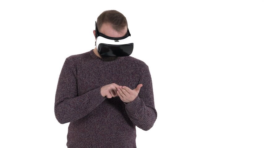 Man imitates smartphone using while wearing VR glasses. Digital age and new technologies | Shutterstock HD Video #1042778542