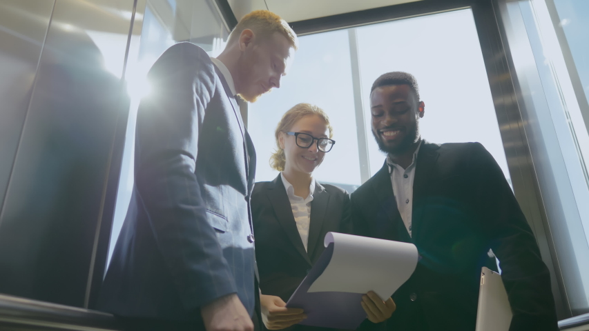 Image of three multicultural businesspeople discussing business plan while riding down in elevator. Collueagues communicate and use their free time descending   Shutterstock HD Video #1042783612