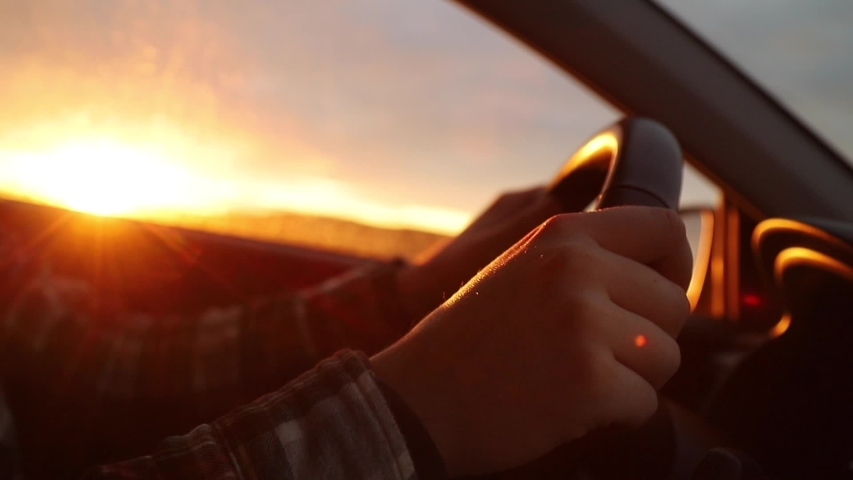 View inside the car on beautiful sunset landscape with mountains covered snow. Close-up view of male hands on the wheel. | Shutterstock HD Video #1042784752