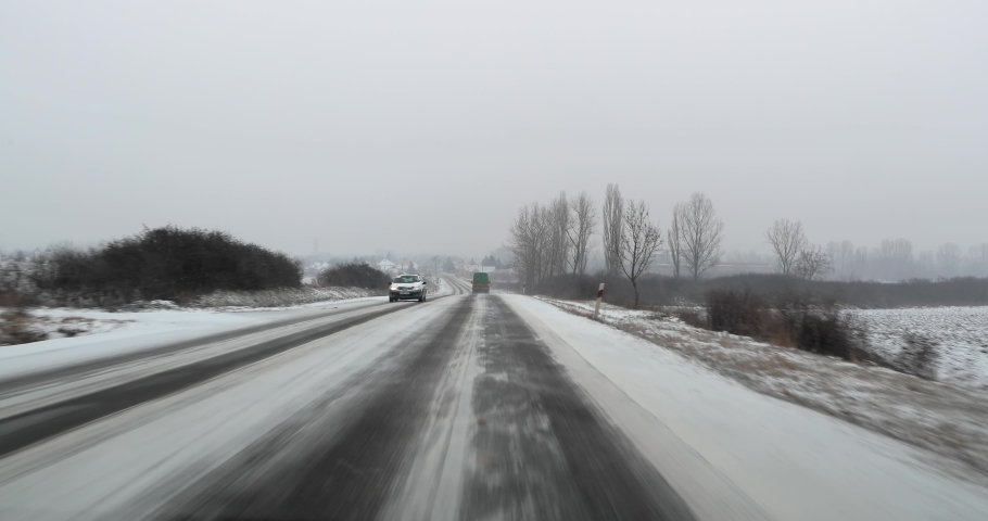 Winter driving on snowy road in falling snow, approaching a village | Shutterstock HD Video #1042792252
