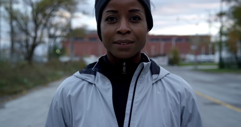Portrait of jogger in hoodie looking content at camera determined and ready to train | Shutterstock HD Video #1042803652