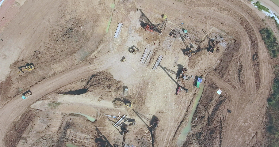 Drone shot looking down at the the  construction site. Drilling piles with heavy machinery and excavator loading sand into a small truck  | Shutterstock HD Video #1042809832