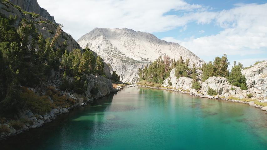 Aerial scenic shot over alpine lake in Eastern Sierra mountain range, California | Shutterstock HD Video #1042860382
