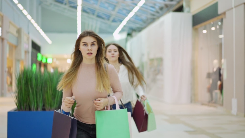 Two shopaholic young women with shopping bags running in slow motion along mall hurrying to make purchases on Black Friday. Woman pushing off her rival to be first in store | Shutterstock HD Video #1043153782