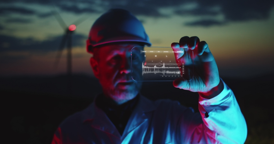 Professional Ecology Engineer holding futuristic gadget cheching efficiency data of wind turbines on background. Future eco technology concept, augmented reality of industrial future development. | Shutterstock HD Video #1043833612