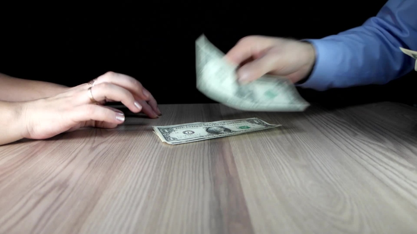 Man puts dollars from his wallet on a table in front of a woman. Concept of paying in cash for a transaction, receiving bribes. The handshake of a male and a female hands and a woman takes the money. | Shutterstock HD Video #1044021232