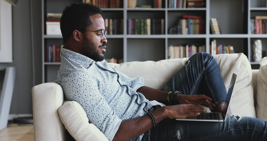 Relaxed serious millennial african ethnic guy student freelancer using laptop device leaning on sofa at home office, focused mixed race entrepreneur working distantly typing on notebook in apartment | Shutterstock HD Video #1044100462