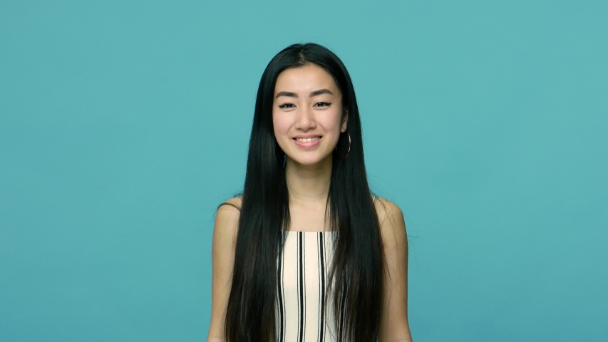 Funny crazy asian woman with long black hair showing tongue and pulling out boogers, picking her nose with stupid comical expression, making faces. indoor studio shot isolated on blue background
