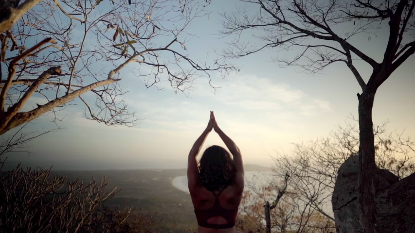 Yoga student sits in namaste pose meditating on a beautiful mountain taking in the peaceful nature setting  | Shutterstock HD Video #1044687262