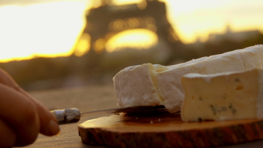 Hand takes a piece of a soft brie cheese from a wooden board on the background of the Eiffel Tower, Paris, France | Shutterstock HD Video #1044717442