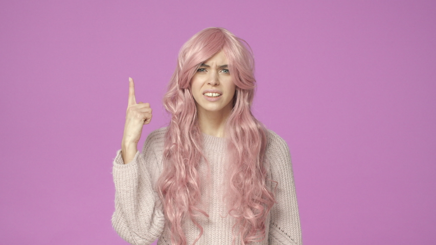 Slow-motion unsure, clueless cute european woman in pink wig, squinting pointing at ear as cant hear anything, asking repeat standing questioned over purple background, dont know what being said | Shutterstock HD Video #1044719572