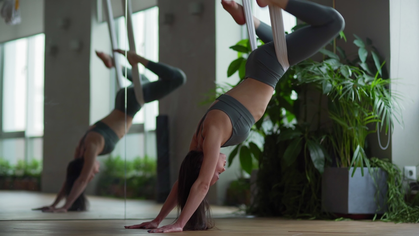 Medium shot of fit young woman doing aerial yoga exercise stretching her back and swinging legs while hanging upside down on hammock in antigravity yoga studio | Shutterstock HD Video #1044725242