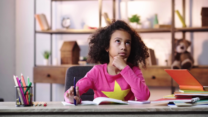 Thoughtful african american child throwing pen and using smartphone | Shutterstock HD Video #1044775552