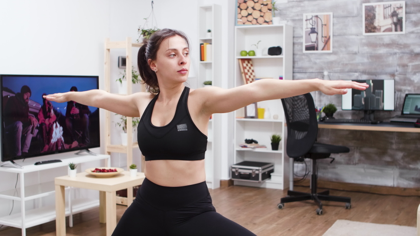 Mid angle of young woman practicing yoga at home in leggings. | Shutterstock HD Video #1044789592