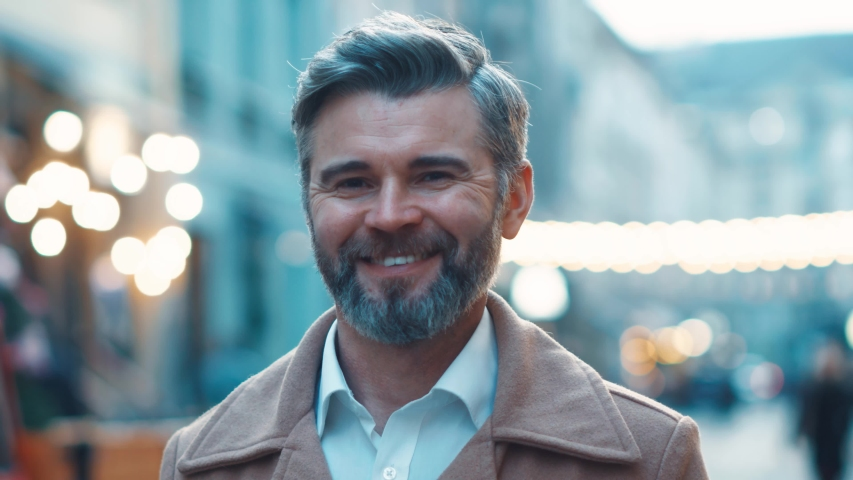 Close up view of middle aged gorgeous business man with grey hair and beard looking to the camera and smile, successful businessman, outdoor, city, lights at background   Shutterstock HD Video #1044817252